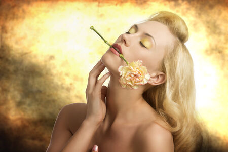 portrait of sensual blonde girl with long hair, colorful make-up and naked shoulders in alluring pose with carnation in her mouth Stock Photo - 23259746
