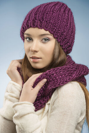 attractive girl with long smooth hair posing with winter clothes, she wearing purple wool hat and scarf and white sweater and looking in camera  photo