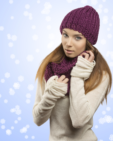 cute young girl posing with winter dress in fashion shot. She looking in camera and wearing purple wool hat, scarf and warm white sweater   photo
