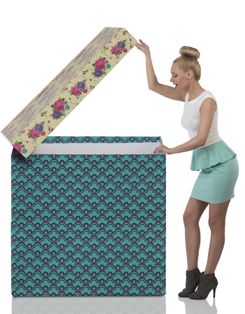 full-length portrait of sexy blonde girl opening big box with expression of surprise , wearing short dress and heels  photo