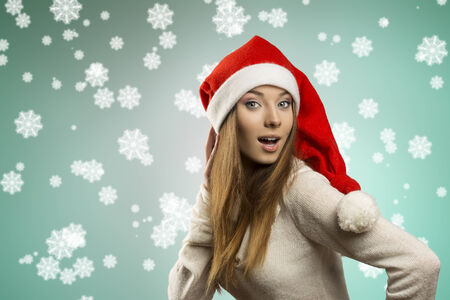sexy young female with long smooth hair wearing warm sweater and funny red christmas hat . Winter xmas portrait  photo