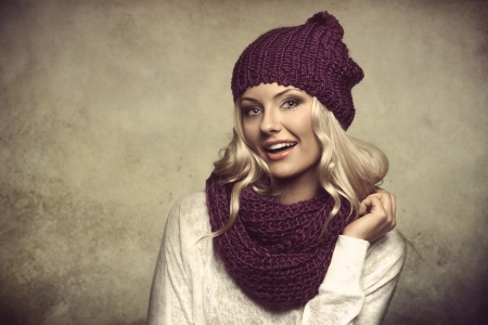 grunge portrait of young and sexy blond girl wearing purple scarf and hat in winter dress over white photo