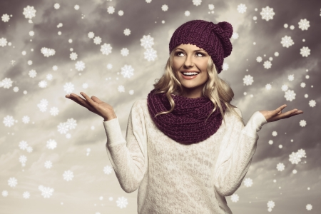 blond girl wearing purple scarf and hat in winter dress under fake snow  in grunge color photo