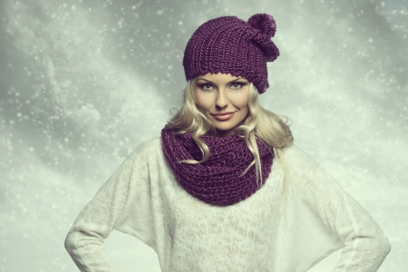 winter girl in white and purple with hat and scarf under snow with cloudy sky in background photo