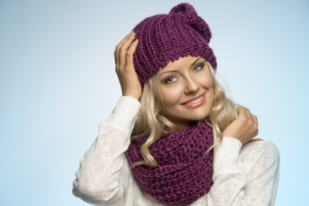 young and sexy blond girl wearing purple scarf and hat in winter dress on light blue background photo