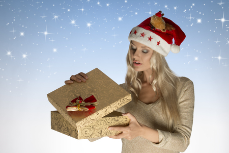 gist: christmas concept shoot of very pretty blonde lady with long har and santa claus hat opening xmas gist box and wearing golden winter sweater