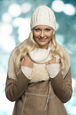 portrait of beauty blonde woman with winter style and long smooth hair. Wearing wool cap, sweater and warm coat, looking in camera and smiling  photo