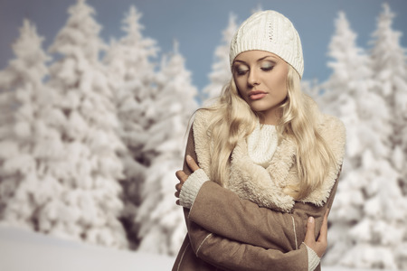 portrait of cold blonde woman in winter season. She wearing warm clothes, white wool cap, sweater and hot coat  photo