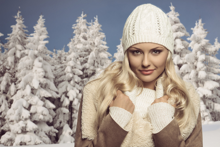close-up portrait of pretty blonde girl in winter season, she posing with wool white hat, sweater and warm coat, smiling and looking in camera  photo