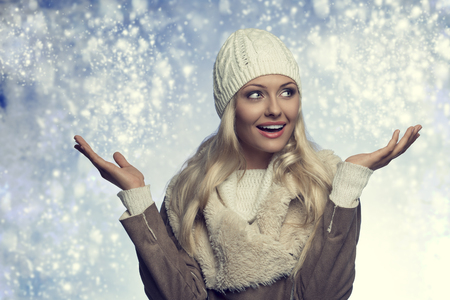 winter close-up portrait of happy blonde lady with warm casual style. She posing with opened arms and smiling, wearing wool white hat, sweater and hot coat photo