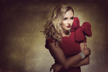 high fashion: blond young woman in red dress and creative hair style , looking on one side. she has a big bow