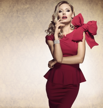 elegante: dame élégante sophistiquée en robe rouge avec un grand arc et des bijoux en regardant la caméra avec une expression arrogante