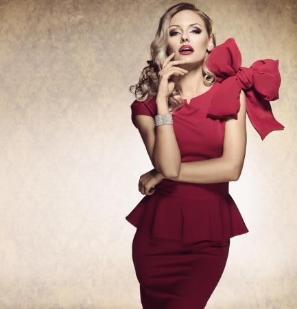 sofisticada dama elegante en un vestido rojo con un gran lazo y joyas mirando en la cámara con una expresión arrogante