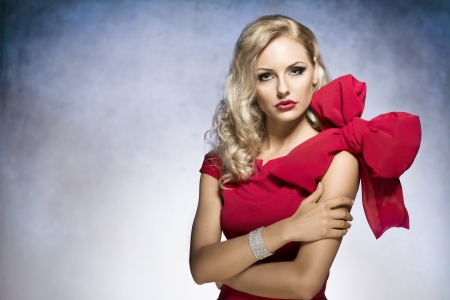 young and sexy beautiful blond woman in red dress with nice hair style and a big bow on shoulder.looking in camera  Stock Photo