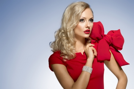 beautiful blond woman in red dress with nice hair style and a big bow on shoulder. she looks somewhere with surprise expression photo