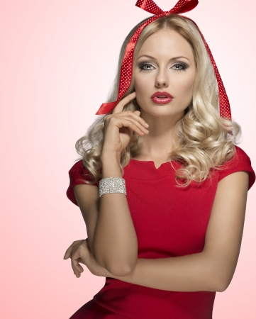 adorned: very sensual blonde female adorned like xmas present with funny bow on her head. Posing with elegant red dress and bright bracelet