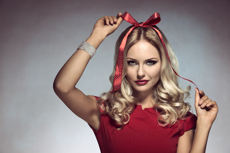 adorned: christmas shoot of funny blonde girl with pois bow on her head, adorned like a xmas gift, wearing elegant red dress and bracelet   Stock Photo