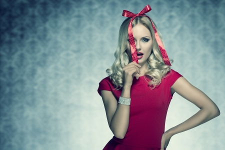 christmas shoot of beauty blonde elegant woman with red fashion dress and bright bracelet posing with funny bow on her head like a present  Stock Photo