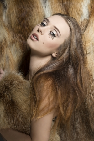 glamour portrait of sexy young girl with long smooth hair, creative make-up on fur background  photo