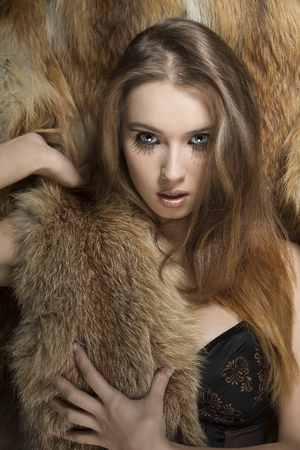 fashion shoot of sensual young girl with creative make-up and long smooth hair, wearing lingerie and fluffy winter fur on her breast. Posing on fur background and looking in camera    photo