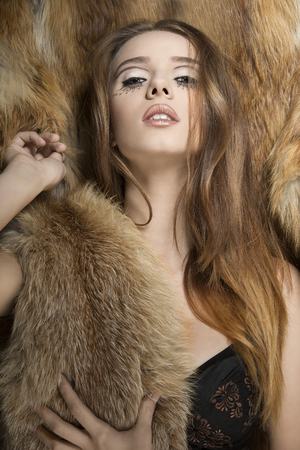 very sexy female posing on fur background with creative make-up and long smooth hair. Wearing lingerie and covering her breast with fluffy fur   photo