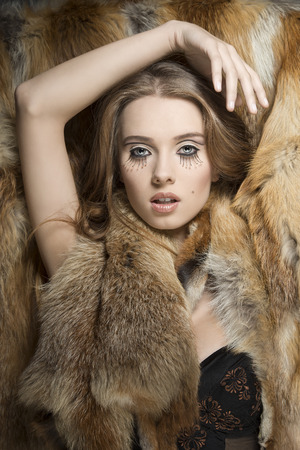 winter fashion portrait of  glamour woman with sexy lingerie, creative make-up and fur. Posing on fur background  photo