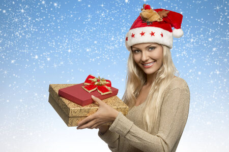 pretty blonde girl with christmas hat and golden dress taking gift boxes in the hands and smiling  photo