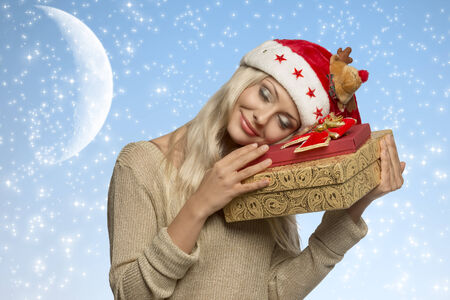 pretty young girl with long blonde hair and calm expression taking gift boxes in the hands, wearing santa claus hat and golden winter dress   photo