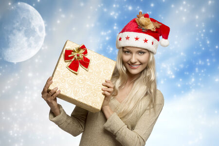 sensual blonde girl with golden dress and funny xmas hat taking gift box in the hands and smiling    photo