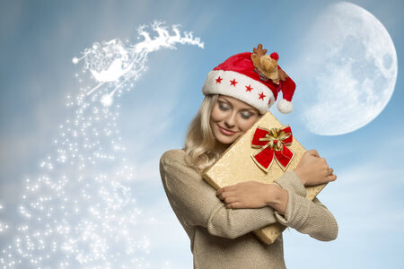 portrait of cute adorable blonde female with christmas hat and golden dress embracing her gift box     photo