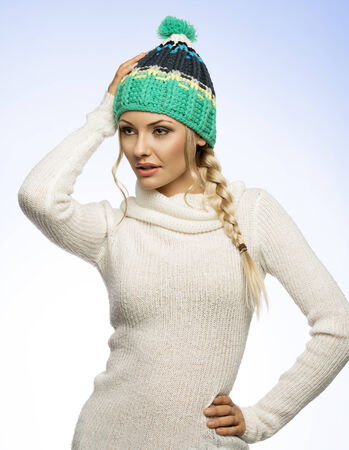 sweater girl: winter blond girl with tress hair and green hat white sweater looking on one side  Stock Photo