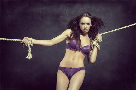 sensual brunette woman with cute body and flying hair tied by rope. Wearing sexy purple lingerie  photo