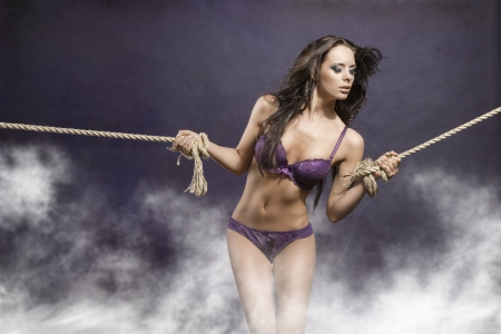 hot portrait of very sexy brunette girl with long flying hair tied by rope. She wearing purple underwear  photo