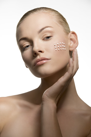 close-up portrait of sensual blonde woman applying white cosmetics on her clear skin. Beauty treatment concept   photo