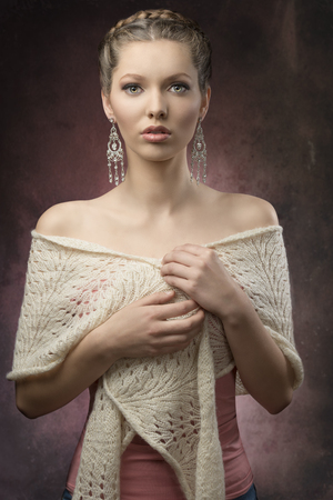 portrait of sensual brunette woman with fashion elegant style, creative hair-style and precious earrings. Covering by wool shawl  photo