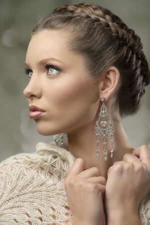 close-up portrait of charming woman with splendid eyes, elegant hair-style, precious earrings and wool shawl    photo