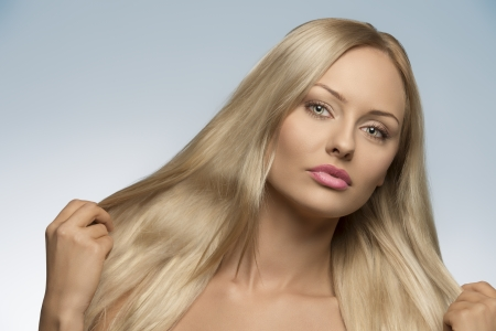 close-up portrait of sensual blonde woman with natural look and perfect skin showing her long smooth silky hair  photo