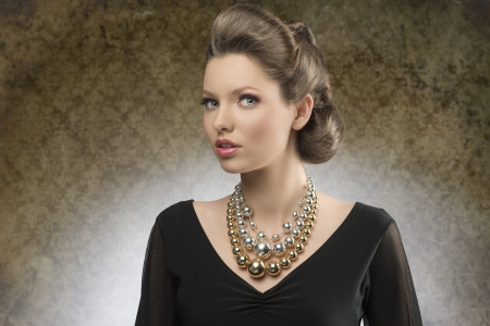 sensual young woman with brown creative hairdo posing in fashion shoot with black dress and bright big necklace   photo