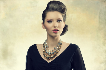 portrait of aristocratic fashion female posing with elegant hair-style, black dress and big necklace. Looking in camera with sensual eyes    photo