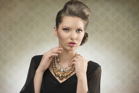 portrait of charming fashion lady posing with brown hair-style, elegant black dress and bright necklace     photo