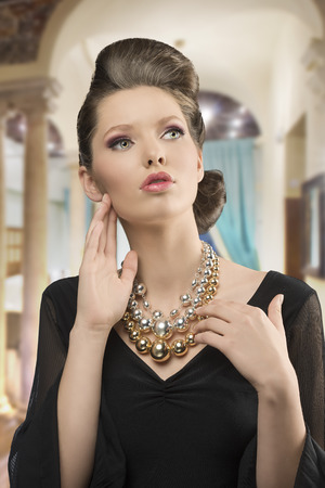 fashion shoot of pretty young brunette girl with elegant style, beautiful hair-style, black dress and big necklace     photo