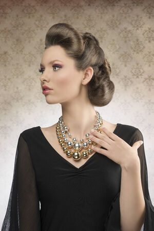 cute brunette woman posing with elegant hair-style, wearing pretty dark dress and big necklace in fashion portrait       photo