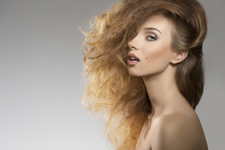 close-up portrait of sexy girl with naked shoulders posing with bushy creative hair-style  photo