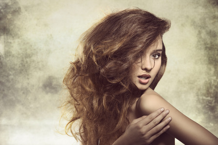 alluring young girl posing in fashion shoot with naked shoulder and creative bushy hairdo  photo