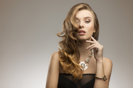 fashion portrait of attractive young girl with elegant wavy hair-style, sexy dress and big golden necklace