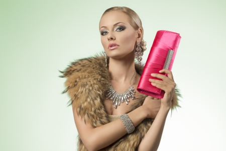 fashion shoot: fashion shoot of sexy blonde woman with luxury style wearing bright  jewellery, fur collar and taking small bag in hand  Stock Photo