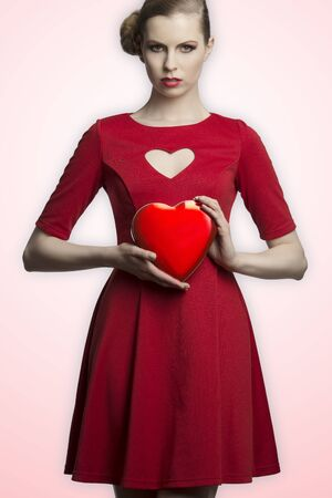pretty blonde girl with creative hair-style and red romantic dress taking in the hands one hearth shaped box  photo