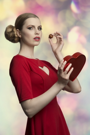 portrait of attractive young girl with pretty hair-style and make-up wearing red dress and taking in the hand her valentine  gift, one box of chocolates   photo