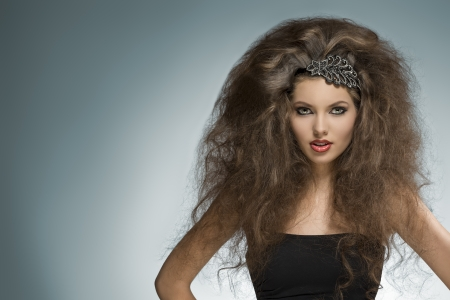 voluminous: sexy brunette girl with long curly voluminous hair-style and glitter accessory in the hair posing in fashion portrait with cute make-up  Stock Photo