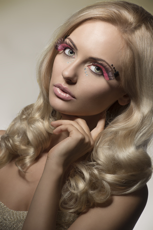 feathered: beauty portrait of splendid blonde woman with pink feathered make-up, glossy decorations, cute wavy hair and perfect skin